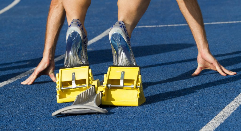 Metafoor voor goede start GoCredible: close-up van de onderbenen van een atleet die in de startblokken klaarstaat voor de sprint.