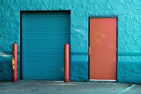 Aankoopbesherming verbeeld met een gesloten rolluik en een gesloten deur ernaast zonder handvat
